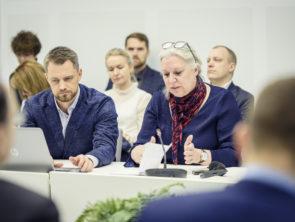 2 cilvēki sēž pie galda un piedalās diskusijā